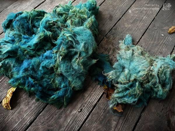 blaugrün gefärbte rohwolle trocknet auf terrasse